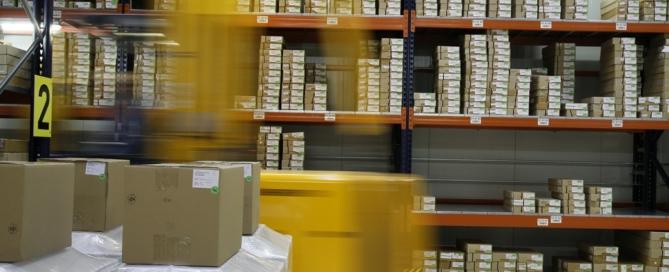 armazém de estocagem de produtos bem organizado com empilhadeira passando na frente